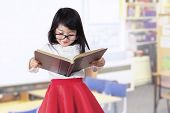 Adorable Girl Reads Book In Class