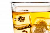 Detail Of Scotch Whiskey In Glass With Ice Cubes On White
