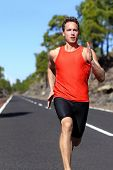 Running man sprinting fast at speed. Male athlete runner sprinter training on road outdoors during workout. Strong male fitness model training outside for in beautiful nature. Strong athletic man.