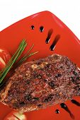 savory on red plate: grilled meat shoulder with tomato and chives isolated on white