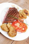 meat savory : grilled beef fillet mignon on white plate with tomatoes , potatoes and chives on woode