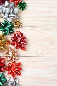 High angle image of a group of colorful holiday bows on a white wood table. Vertical format with copy space.