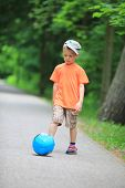 Boy Kicks The Ball In Park Outdoors
