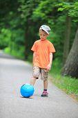 Boy Kicks The Ball In Park Outdoors