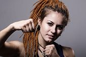 Close-up Portrait Young Woman With Dreadlocks In A Fighting Stance With His Fists.