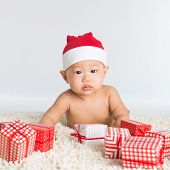 Asian santa hat baby boy with Christmas present on floor.