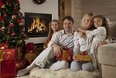 Family Sitting By Christmas Tree