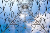 stock photo of utility pole  - In the center of high voltage power pole seeing the top of voltage tower and clear blue sky background - JPG