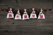 Presents with hearts hanging on wooden background for birthday, christening, valentine or christmas.