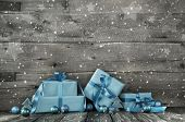 Grey wooden christmas background with a stack of presents in blue or turquoise.