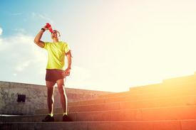 picture of dark-skin  - Attractive dark skinned runner at sunny evening resting after intensive training - JPG