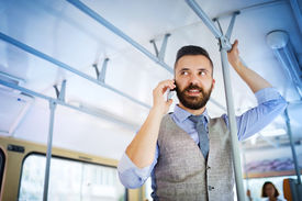 stock photo of tram  - Handsome hipster modern man calling by mobile phone in tram - JPG