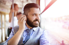 stock photo of tram  - Handsome hipster modern man with headphones traveling by tram in town - JPG