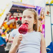 Adorable little girl having fun at fairground, eating red candy apple