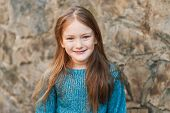 Outdoor portrait of a beautiful little girl of seven years, wearing blue pullover