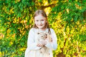 Portrait of adorable little girl with bunny toy, outdoors sunset
