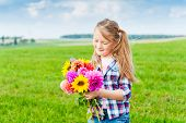 Outdoor portrait of adorable little girl playing with flowers in a field in countryside on a nice su