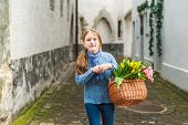 Outdoor portrait of adorable little girl of 7 years old walking in old town, holding basket full of