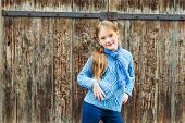 Outdoor portrait of a cute fashion little girl, wearing warm blue pullover and scarf, standing again