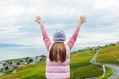 Kid girl stand between Lavaux vineyards looking at the view with arms open