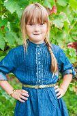 Outdoor portrait of a cute little girl wearing denim dress with golden  accessories