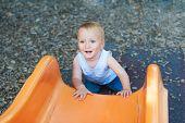 Adorable toddler boy having fun outdoors, climbing on playground