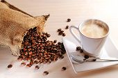 Cup Of Hot Coffee On Table And Sack With Coffee Beans
