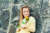 Outdoor portrait of a cute little girl of 7 years old with sunflower