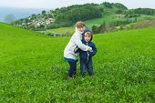 Two adorable kids playing in a field, hiding from coming storm