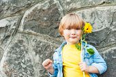 Outdoor portrait of a cute little boy holding sunflower