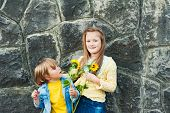 Outdoor portrait of adorable kids outdoors, holding sunflowers