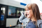 Little girl talking on a phone in a city