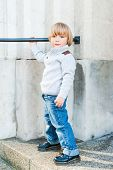 Outdoor portrait of a cute toddler boy, wearing grey pullover, jeans and black boots