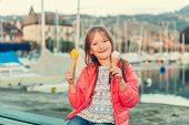 Adorable little girl eating ice cream outdoors, sunset