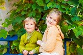 Adorable children resting outdoors, wearing knit pullovers