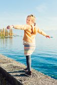 Outdoor portrait of a cute little girl walking next to beautiful lake