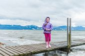 Cute little girl playing outdoors next to lake on a cold weather, feeding birds