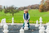 Adorable toddler boy playing with huge chess in a park on a cold day