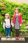Outdoor portrait of adorable children next to school
