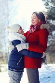 Life Portrait Of Happy Family, Son Hugs His Mother In Sunny Winter Day