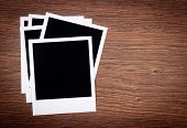 blank photo frames on wooden background