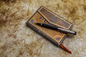Aged Book With Ornamented Covers And Pen