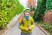Cute little girl walking in an alley on a cold autumn day