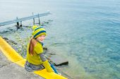 Cute little girl resting outdoors, sitting on the edge of the lake on a cold day