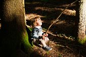 Adorable toddler boy hiking in the forest on a nice day