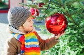 Adorable little boy playing with christmas tree outdoors