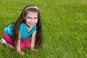 Joyful Little Girl On The Grass