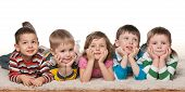 picture of lie  - Group of five joyful children are lying on the floor on the white carpet - JPG