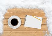 Coffee, pencil and notebook on the planks covered with snow