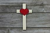 Wooden cross with red heart on rugged wood background